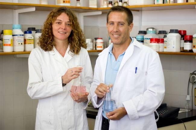 La Dra. Paula Castillo Hernández y el Prof. Rafael Prado Gotor sostienen nanopartículas dispersas y agregadas respectivamente obtenidas in situ en su laboratorio de trabajo.