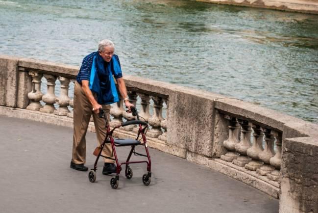 Un hombre camina con una ayuda junto al río Sena