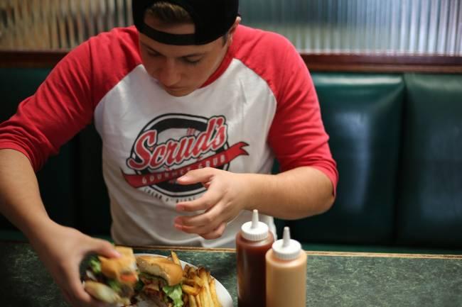 adolescente comiendo una hamburguesa