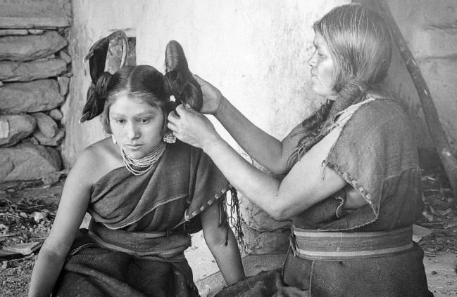 Una mujer hopi arregla el peinado de una soltera de su tribu. / Wikipedia