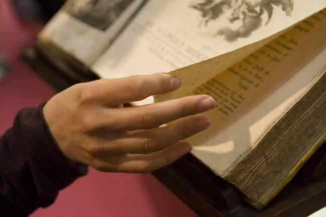 Unas manos pasando las hojas de un libro antiguo
