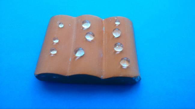 Teja tras ser tratada con el material superhidrofugante. Las gotas tienen una forma totalmente esférica, con lo que se reduce el área de contacto entre el agua y la teja, permitiendo que las gotas rueden / Fundación Descubre