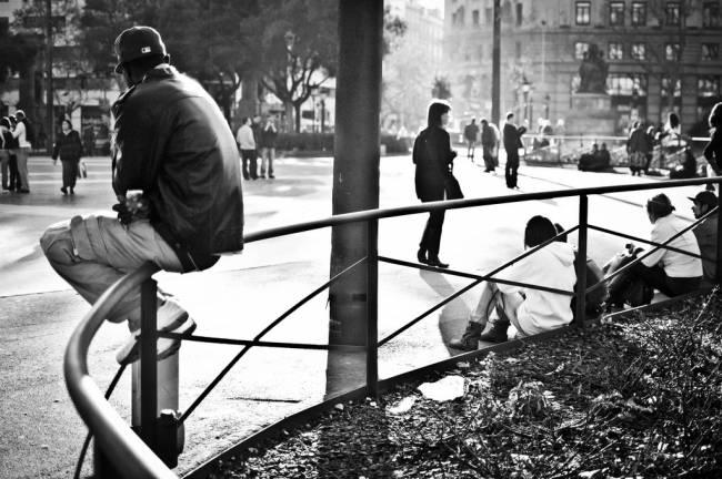 Joven sentado en una plaza de Barcelona. / David Flores