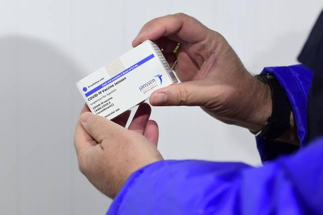 persona con la caja de la vacuna de Janssen