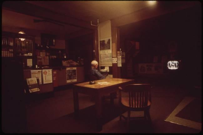 Fotografía en penumbra de una persona mayor viendo la televisión en un bar.