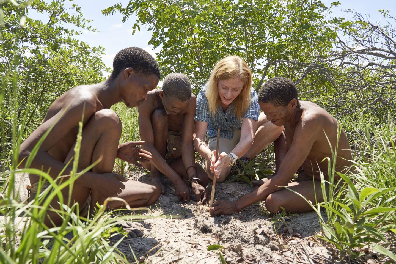 La investigadora Vanessa Hayes aprendiendo a hacer fuego con la población local de cazadores hoansi en la tierra natal ahora seca del gran Kalahari en Namibia / Chris Bennett